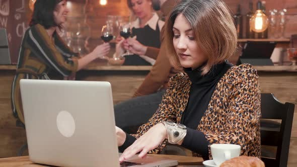 Woman Entrepreneur Typing a Text on Her Laptop While Working in a Coffee Shop