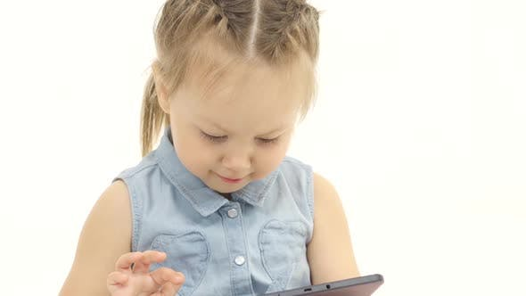 Thumbnail for Little Child Looks Interesting Pictures on the Tablet. White Background