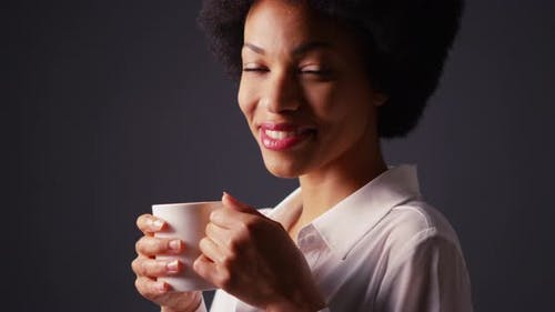 Black woman with afro in studio drinking hot coffee and smiling