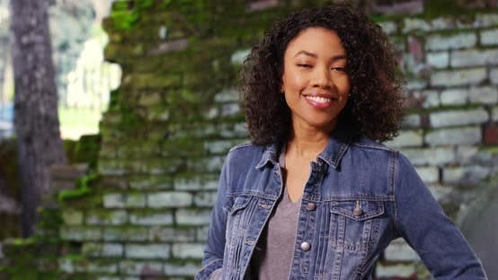 Thumbnail for Cute African female with curly hair smiling at camera cheerfully outdoors