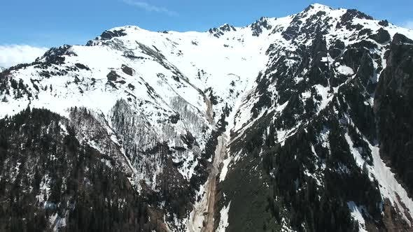 Thumbnail for Flight From Green Meadow on Plateau to Snowy Mountain Valley