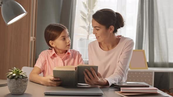Woman Helping Child with Homework