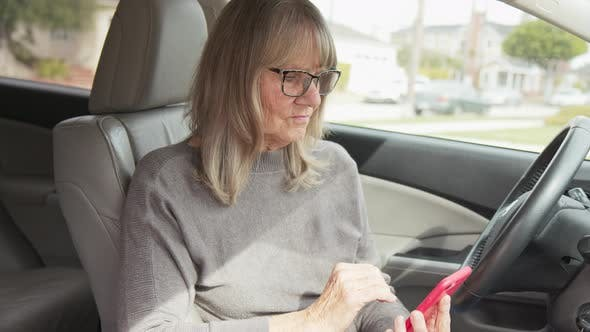 Driver looking for destination address and checking map app on her phone in car