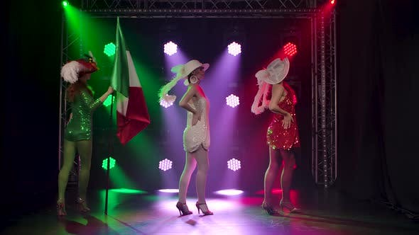 Thumbnail for Three Chic Cabaret Dancers in Short Glittering Dresses Perform in a Dark Studio Against a Backdrop