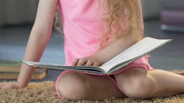 Female Child Sitting on Carpet and Reading Fairy Tales