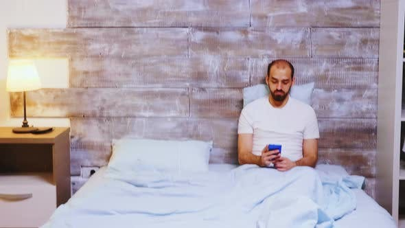 Thumbnail for Guy Browsing on Smartphone in His Bed