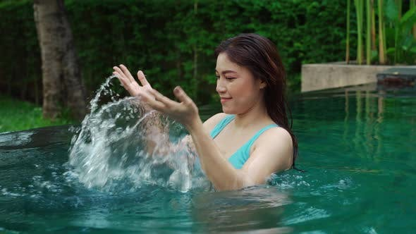 young woman enjoying and walking in swimming pool