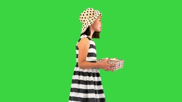 Beautiful Little Girl a Gift Box Walking on a Green Screen Chroma Key