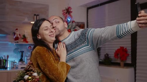 Festive Couple Taking Pictures on Smartphone Feeling Cheerful