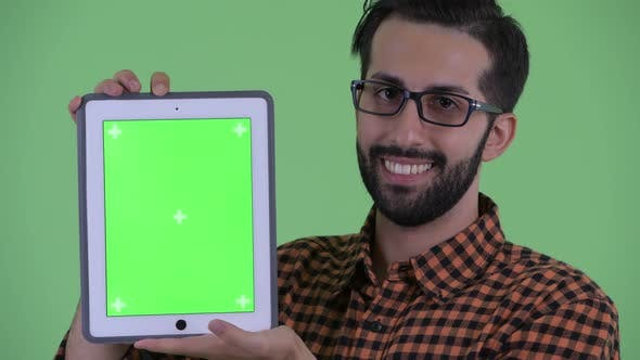 Thumbnail for Face of Happy Young Bearded Persian Hipster Man Talking While Showing Digital Tablet