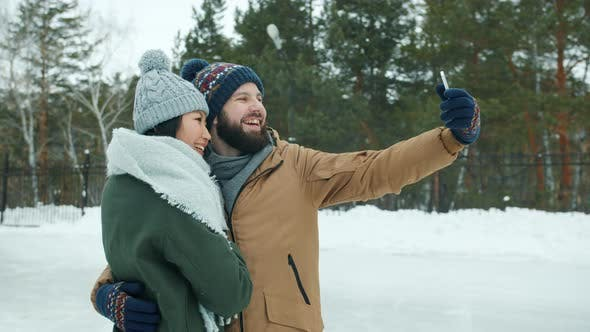 Happy Young Multi-ethnic Couple Taking Selfie at Skating Rink Posing for Smartphone Camera