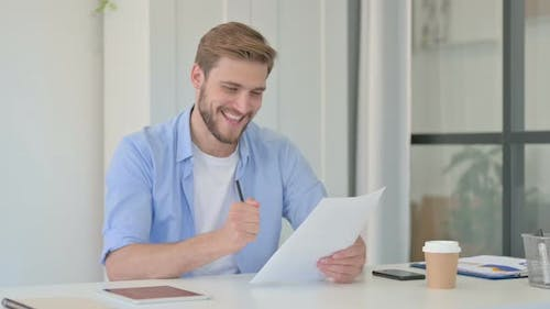 Young Creative Man Celebrating Success While Reading Documents
