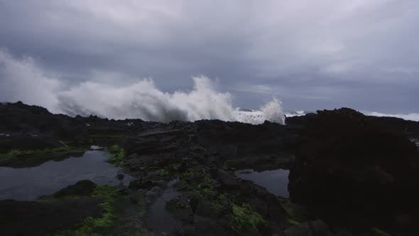 Thumbnail for Panning view of waves shooting up on rocky beach