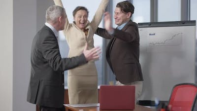 Excited Group of Colleagues Rejoicing and Hugging in Office