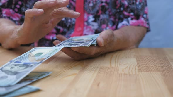 Thumbnail for Dolly Shot Hands of Elderly Grandmother Holds Bundle of Money and Scatters Foreign Currency on the