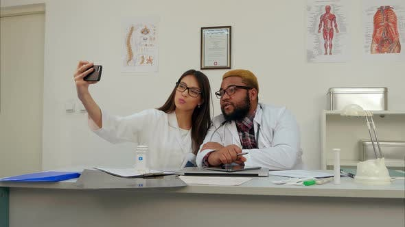 Thumbnail for African American Doctor and Pretty Nurse Taking Silly Selfies on the Phone