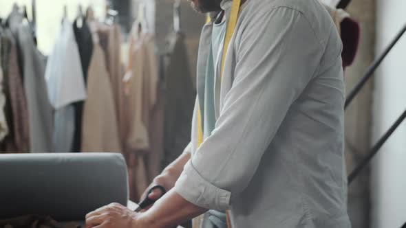 Male Tailor Cutting Fabric in Dressmaking Studio