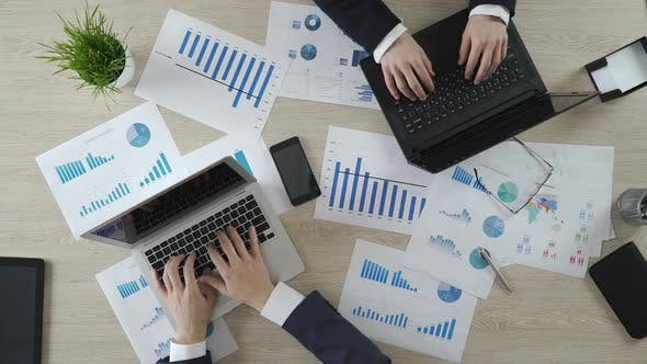 Thumbnail for Zwei Unternehmens- mitarbeiter schreiben auf Laptops, Arbeiten an Geschäftsprojekten, Draufsicht