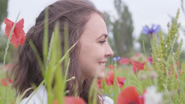 Thumbnail for Close-up Portrait Cute Girl Sitting in Poppy Field. Cute Happy Smiling Girl Resting Outdoors
