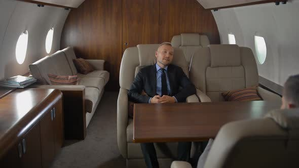 Private Jet Cabin with Businessman in Armchair. He Have Conversation with Partner.