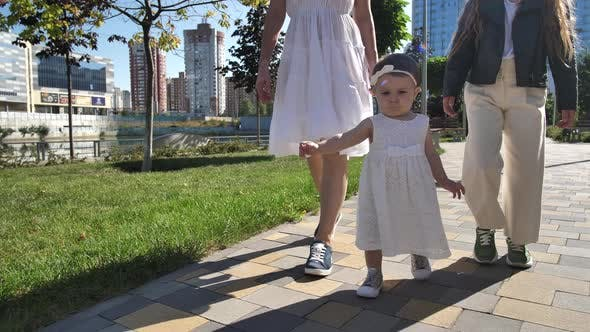 Adorable Baby Girl Learning To Walk in Urban Park