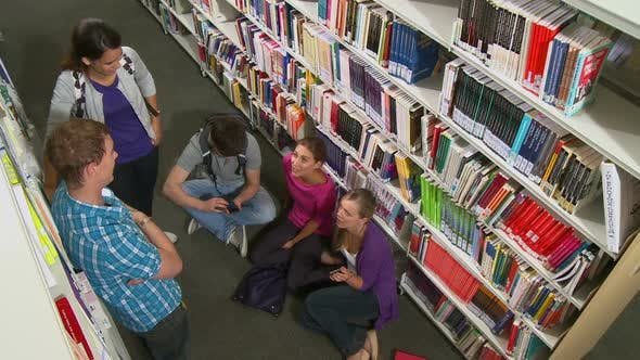 Thumbnail for Student talking between bookshelves in library