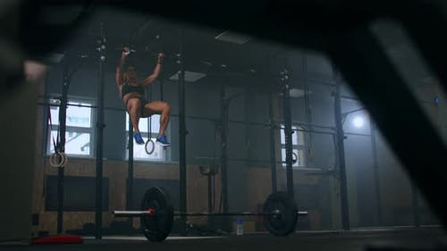 A Strong Athletic Woman Performs pull-UPS on a Horizontal Bar in the Gym. Workout