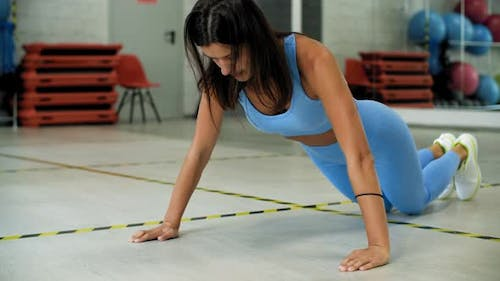Fitness Woman Training Push Up Exercise on Floor in Sport Club. Sporty Woman Pushing Up on Knees on