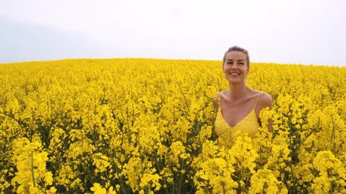 Blonde Woman Walking Across a Great Plains of Canola Flowers