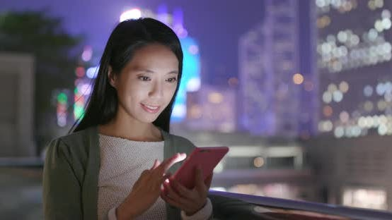 Thumbnail for Woman sending message on cellphone in Hong Kong at night