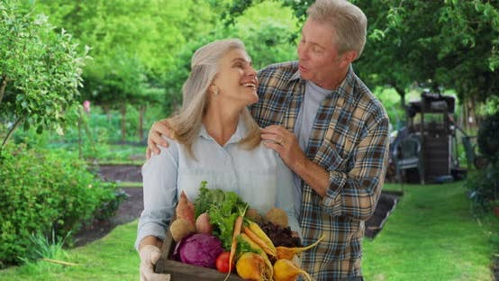 Thumbnail for Happy aged white gardener couple stand proudly with produce from private garden
