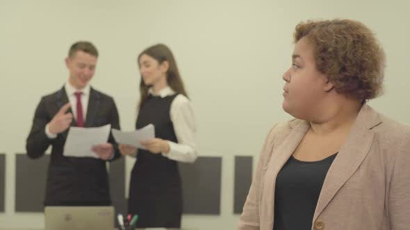 Thumbnail for Portrait of Plump Woman in Formal Wear Looking in the Camera in the Foreground in the Office While