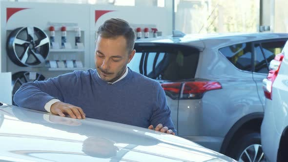 Thumbnail for Business Man Examines the Car in the Car Showroom