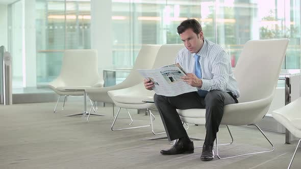 Thumbnail for Businessman reading a magazine then looking at the camera
