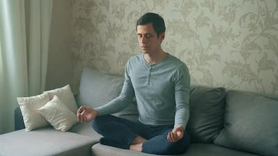 A Man Sitting on the Couch Meditates