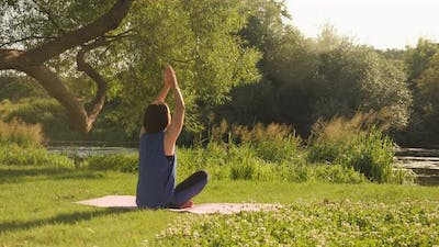Morning meditation at sunrise. Practicing yoga in park in the morning.