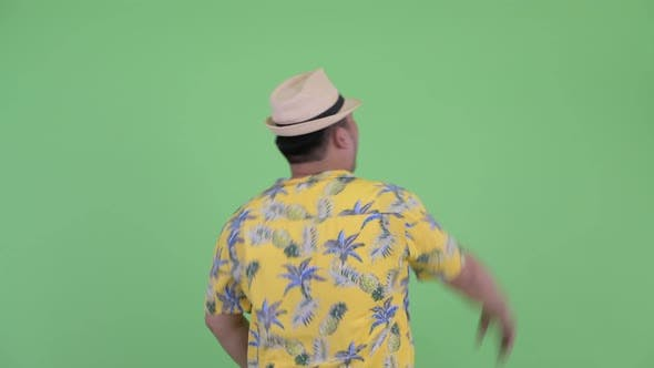Thumbnail for Rear View of Happy Young Overweight Asian Tourist Man Pointing Finger