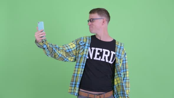 Cover Image for Portrait of Happy Nerd Man Video Calling with Phone