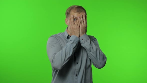 Thumbnail for Shy Guy Scared To Watch. Man Covering Eyes with Hands and Looking Cautiously Curious at Camera