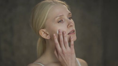Closeup Beauty Portrait of Young Woman with Long Hair and Perfect Skin Applies Cream on Her Face