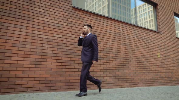 Thumbnail for Emotional Smiling Young Man Talking on Smartphone Outdoor. Excited Businessman Happy To Hear Good