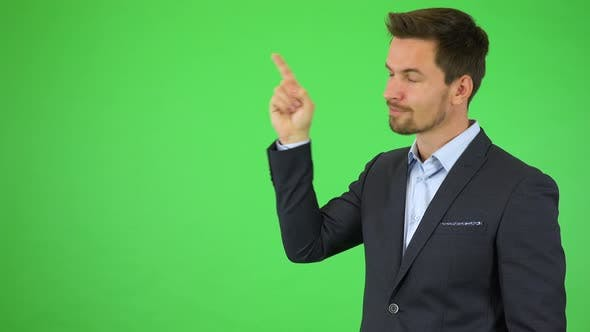 A Young Handsome Businessman Points at Bullet-point Text, Smiles and Nods - Green Screen Studio