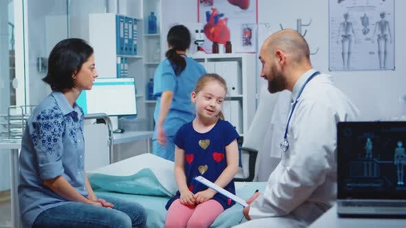 Thumbnail for Doctor Talking with Little Girl Sitting on Bed