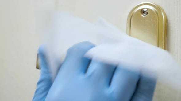 Close Up View of Hand in Medical Glove Using Antibacterial Wet Wipe for Disinfecting Room Door Knob