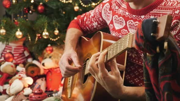 Thumbnail for Male hands are playing guitar at home on Christmas eve sitting near decorated New Year tree