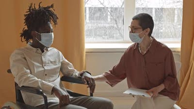 Black Man in Wheelchair Talking to Psychologist