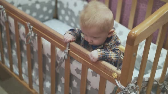 Little Baby Leans on Wooden Cot with Soft Linen at Home