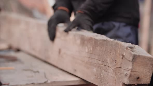 Close-up View of Unidentified Worker in Work Gloves Turning Over Thick Sawing Board with Grinder