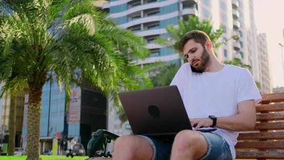 Thumbnail for A Man in a White T-shirt with a Laptop Talking on the Phone in the Summer on the Bench