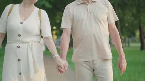Unrecognizable Elegant Mid-adult Man and Woman Holding Hands and Strolling in Summer Park. Loving